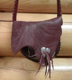 """9"""" x 8"""" Rosewood 8 oz. Buffalo Purse. This purse has two pockets with one being edged with burgundy sheepskin. Both pockets have silver-tone beads laced into stitching. Strap measures 50"""" and is a cross-over with one edge hand laced with redwood lambskin. Closing flap has a silver-tone heart concho with fringe."""