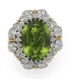 A PERIDOT, DIAMOND AND GOLD RING Of bombé design, set with an oval-cut peridot, within a circular-cut diamond surround, further enhanced by circular-cut diamond leaves with 18k gold veining, to the textured 18k gold hoop, mounted in 18k gold and platinum