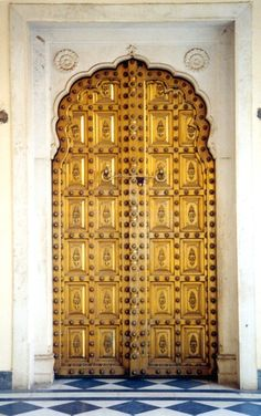 Fantastic yellow carved double doors surrounded by what appears to be white marble that scallops the arch.