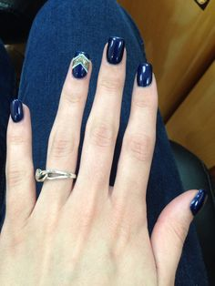 Acrylic nails with a navy blue that has red speckles in it, with a gold and white design on the ring finger