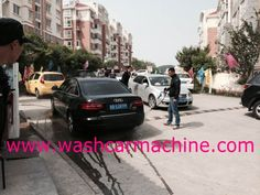 People clean a car in the public by a coin operated car wash, http://www.washcarmachine.com/.