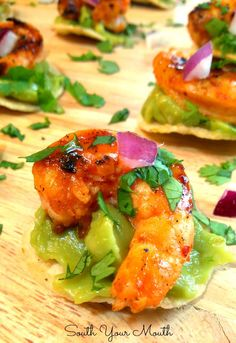 Chipotle Shrimp Tostada Bites! Super fun and easy mini tostadas made with tortilla chips, chipotle glazed shrimp and guacamole sprinkled with a confetti of red onion and cilantro.