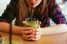 Girl drinking a green smoothie stock by Kasia Górska on @creativemarket