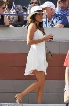 Eva Longoria in a white coloured chiffon mini-dress, complete with pleats, with an ivory fedora and Chanel nude strappy sandals