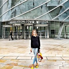 Olivia Palermo wears a black top with distressed light blue skinny jeans, yellow flats and a yellow bag.