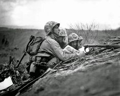 History in Photos: World War II. Observer who spotted a machine gun nest finds its location on a map so they can send the information to artillery or mortars. Iwo Jima, February 1945