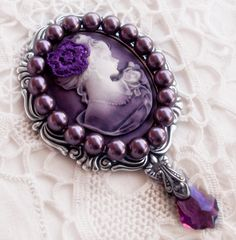 This is so lovely... purple pearls... cameo...some silver... and what is that little flower made of?  Wait a minute - this is a brooch?  I thought it was a mirror!