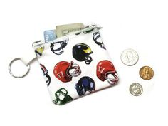 Football theme pouch, football coin purse, coin purse keychain, zippered pouch, football player gift, under 10 gift, stocking stuffer READY TO SHIP  40% off sale!  Football and sports lovers will love this handy coin purse keychain. This sports themed coin purse is made from a cotton fabric that features colorful football helmets on a white background. The purse is fully lined with an white cotton fabric and has a matching white zipper. A key ring is attached to the purse to make it easy to…