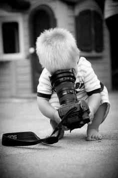 És una foto on surt un nen ajupit amb una càmera de fotos a les mans. Es veu que aquesta experimentant amb ella i l'objectiu de la càmera se'l posa a la cara. És una imatge divertida en blanc i negre.