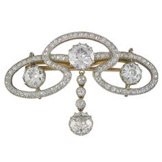Edwardian Diamond Scroll Brooch. An Edwardian diamond scroll brooch, the brooch comprising three old brilliant-cut diamonds, within a flowing openwork diamond-set scroll surround, with old brilliant-cut diamond drop to the centre, the diamonds estimated to weigh a total of 3.2 carats, all set in silver with grain edging to a yellow gold mount and brooch fitting, gross weight 7.1 grams, circa 1900