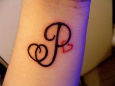 Slim curled dark black P letter and tiny red heart wrist tattoo