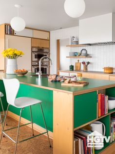 This modern kitchen with 1960s style featured a green laminate kitchen island, a white tiled backsplash and bulb pendants. Take a full tour on HGTV.com.