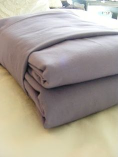 How to fold sheets into neat packages that actually sit pretty on linen closet shelves...including the pesky fitted sheet!