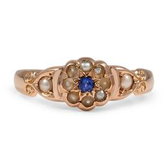 The Alick Ring.  This Victorian halo ring features a vivid natural sapphire encircled by eight seed pearl accents.