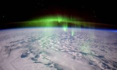 Glowing green aurora over clouds on Earth photographed from orbit