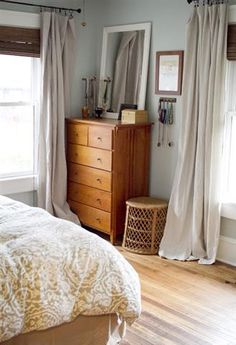 From a view along the way: I love the drop-cloth curtains and how they pool on the floor. The bamboo shades are cool too. I also like the hanging necklaces to the right of the dresser.