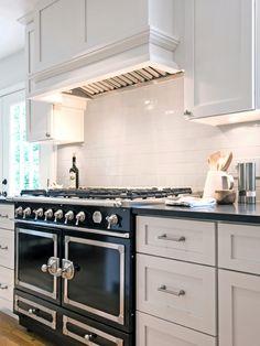 Gorgeous kitchen with La Cornue CornuFe Range in Gloss Black and white wood paneled kitchen hood.