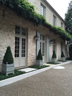 Motor court entry to a home with limestone, gravel and Versaille Tub planters of Boxwood by Howard Design Studio.