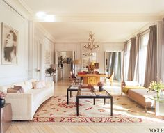 L'Wren Scott and Mick Jagger's turn-of-the-century Left Bank apartment in Paris. A curved sofa in cream bouclé wool from the 1940s, found in a shop on Rue de Lille, imbues the drawing room with soft, pale undertones; the other end pairs Damien Hirst's spots with a medieval wooden saint on a 1930s table by André Arbus.