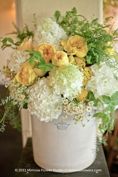 Soft mopheads of white hydrangeas (a mix of Annabelle Hydrangea and White Bigleaf Hydrangea) are the ideal foil for golden garden roses and snips of yarrow, ferns, and daisies.