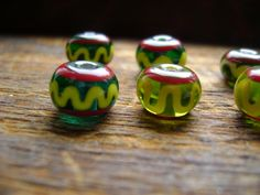 Bead Pattern 29: Green Viking bead with yellow and red lines (reproduction) by heartofoakcrafts on Etsy https://www.etsy.com/listing/107283191/bead-pattern-29-green-viking-bead-with