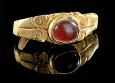 A gold ring with a red glass stone, Roman, 3rd century A.D.