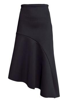 Falda asimétrica: Falda en punto de aspecto neopreno con elástico oculto en la pretina y parte inferior asimétrica con costuras sin rematar. Sin forrar.