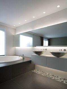 Idées déco pour une grande salle de bain principale contemporaine avec un placard à porte plane, des portes de placard blanches, un sol en carrelage de céramique, un mur gris, une vasque, un carrelage gris et une baignoire posée.