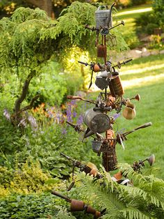 Flotsam and jetsam -- wreckage or things cast aside -- become a stationary metal tree when grouped together on a tall pole with varied arms. Use different types of materials -- chipped porcelain, old wicker, rusted metal -- for surprising depth in the back of a flowerbed.
