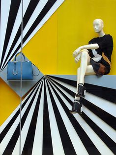 "Fendi, Window Display: great use of contrast and linear eye-paths... If the grey shelf holding the bag had been painted to match the yellow background (making that blue ""pop""), more attention would go to the bag!"