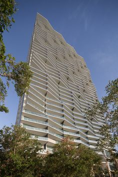 American firm Arquitectonica has completed a residential tower in Miami with a crinkled facade and a public park that passes underneath the raised building.