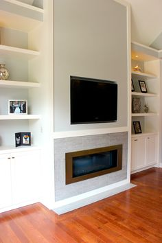 White living room wall unit with built-in television and gas fireplace insert. Combination of open shelving and lower cupboards.