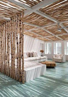 wohnzimmer mit strand birken stämme und strahlend weiße sitzmöbel