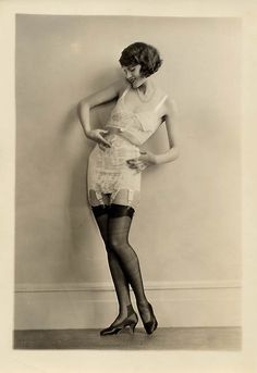 1920s photo by Charles Gates Sheldon. From what I can see, women wore a corset around the waist (if at all) to shape their midsection with garters connected to it to hold up their stockings. Underneath that, they either wore a bra or a slip. Some of the slips were all-in-one, meaning they included underwear as a bottom part.