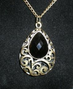 "Beautiful vintage style, black teardrop shaped pendant. It has a black Lucite, faceted ""gem"" in the center.     The teardrop shaped pendant has a beautiful scrolling filigree design reminiscent of old style jewelry.     On the back of the pendant are very small teardrop shaped openings.     Pendant is .37"" inches thick, 2"" inches long, and 1.37"" inches wide, chain is 31"" inches long.     Ships out the Los Angeles area, from a smoke free home."