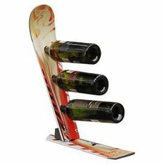 """An innovative way to display your favorite vintages, this handmade wine rack is artfully crafted from reclaimed skis and holds 3 bottles. Made in USA.   Product: Wine rackConstruction Material: Reclaimed stainless steelColor: Nordica tequilaFeatures:  Made from used, slightly weathered skisBottles are stored on their sides to properly maintain the wine's integrityWeather-resistantHolds three bottles Dimensions: 18"""" H x 6"""" W x 16"""" DNote: Due to the re-purposed construction of this product…"""