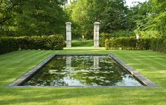Romantic Country Garden Design in Surrey with formal rectangular reflecting pond in lawn and stone pillars