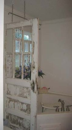 Old Chippy Door...hanging from the ceiling as a room divider. Try to find 2cheap ones hang on barn door track in front of sliders, leave room at bottom for Blake to look out  windows in them would be great ,so we could see out!