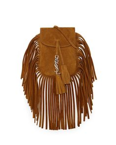 """Saint Laurent suede """"Anita"""" shoulder bag with fringe trim. Silvertone hardware. Shoulder strap with 23.6"""" drop. Rounded flap top with YSL metal and tassel detail. Hidden snap closure. 7.9""""H x 4.1""""W x"""