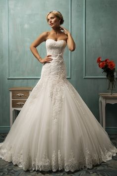 Wedding dress Arabella - AmeliaSposa. This unusually too bouffant skirt in a mermaid silhouette freshens a classic look making it lighter. A key accent put on handmade laces and delicate cleavage make the dress a little less seductive adding grace and glamorous chic to a bride's look.