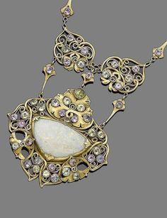An early 20th century Arts and Crafts gem-set pendant necklace, by A.H. Anderson for the Elverhoj Colony The wide navette-shaped plaque set with a triangular-shaped opal, in closed back-setting, within an intricate openwork scrolling surround accented by circular-cut gemstones including sapphires, chrysoberyl, and aquamarine, suspended from two similar plaques, to a figaro-link chain, signed Elverhoj.