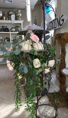 Romantic, gardeny and fairytale. Hanging iron cage with flowing greens and roses. Contact Marion at Bayview florist wedding studio in Sayville, NY. Maz851@aol.com