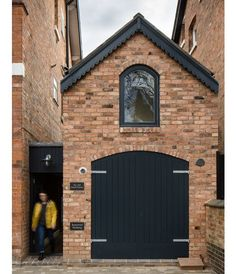 Faux timber doors painted black along with a brick facade help the dwelling blend with its surroundings: the Victorian homes of the Moseley neighborhood in Birmingham UK. Photo by Paul Miller Architecture by by dwellmagazine Brick Shed, Brick Siding, Brick Facade, This Old House, Tiny House, Architecture Design, Casa Loft, Mews House, Timber Door