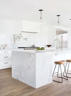A waterfall counter top turned traditional. This twist on the modern waterfall counter top provides an excellent separation of space between kitchen and bar.   Tessa Neustadt Interiors