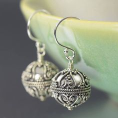 Bali style earrings featuring round textured dangle with an antiqued blackened finish. These light weight beads dangle freely form sterling silver earwires. shopsouthpaw.com