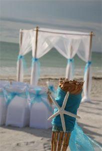 Tiffany blue sash detail and a white starfish decorate a tiki to mark the aisle ... Florida beach wedding style by Suncoast Weddings