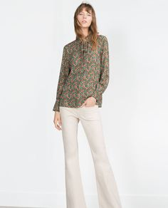 Rock the 70's Trend in a printed high neck top and flared pants.
