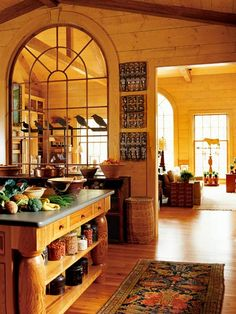 Arched window separating the kitchen and living room...good idea.