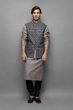 Self weave kurta with waistcoat  This self weave kurta comes with a grey waistcoat and a black churidar. The waistcoat has black resham jaal embroidery. The kurta and the waistcoat are neatly finished with a black piping.