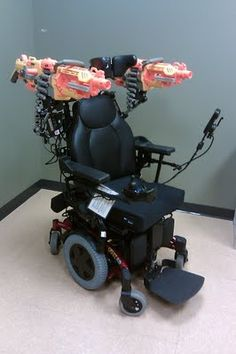 """AWESOME!!!!    You might ask yourself, """"Why would anyone mount dual Nerf machine guns on a wheelchair, and hack it to fire them from the drive controls?""""  I might ask you why you hate fun.  (medically necessary adaptations, lol)"""